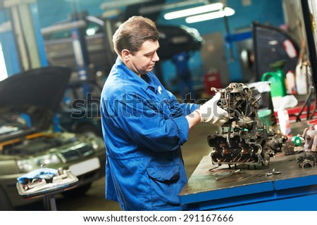automotive mechanic worker works with engine or gearbox during automobile car maintenance at  repair service station - stock photo