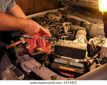 Automotive technician doing repair job. Replacing part. - stock photo