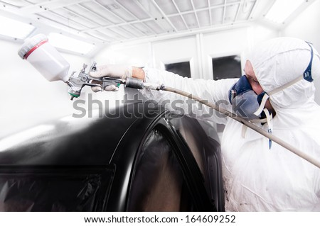 automotive worker painting a black car in a special booth