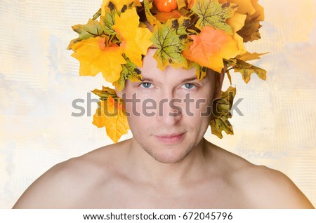 Autumn. A handsome man and orange foliage. Day. The sun.