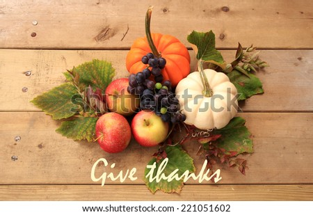 "Autumn and Thanksgiving concept. Seasonal fruit and pumpkins on wood background with the phrase ""Give thanks"" at the bottom. - stock photo"