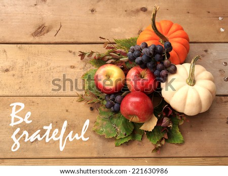 "Autumn and Thanksgiving concept. Seasonal fruit and pumpkins on wood background with the phrase ""Be grateful"" on the left.  - stock photo"