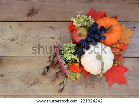 Autumn and Thanksgiving concept. Seasonal fruit, flowers, leaves and pumpkins on wood background. - stock photo