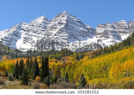 Autumn at Maroon Bells - Peaks of Maroon Bells surrounded by colorful autumn aspen grove and evergreen forest. Aspen, Colorado, USA. - stock photo