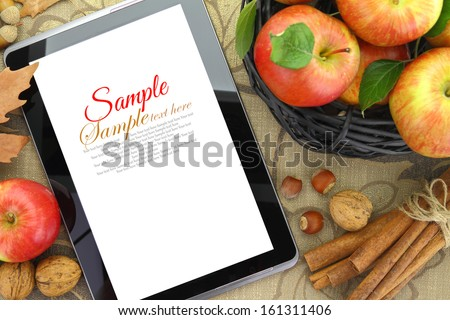 Autumn background basket with apples and tablet - stock photo