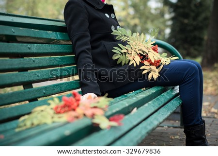 Autumn background / Beautiful young girl sitting on a bench in autumn park, holding a branch of mountain ash / Thanksgiving day concept