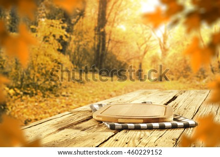 autumn background of desk napkin and wooden table in garden