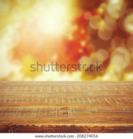 Autumn background with beautiful bokeh and wooden table - stock photo