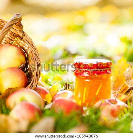 Autumn background with jam in jar and red juicy apples on yellow leaves outdoors - stock photo