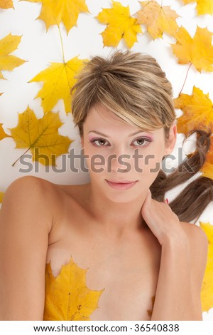 Autumn beauty. Portrait of attractive nudity woman covering by maple leafs - stock photo