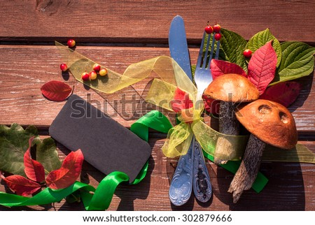 Autumn border from mushrooms, berries, cutlery and fallen leaves on old wooden table. Thanksgiving day concept. Background with tag/ sticker/ with copy space for your text. Happy Thanksgiving day. - stock photo
