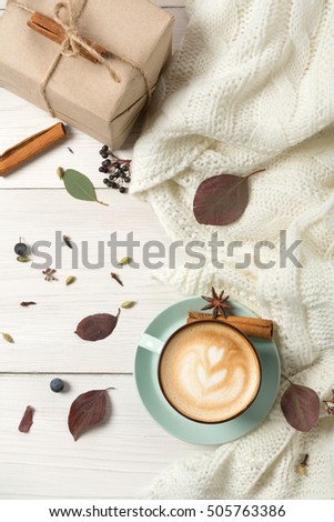 Autumn cappuccino composition. Blue coffee cup top view with foam, cloves, cinnamon, present box and warm sweater at white wood background with copy space on paper sheet. Fall hot drinks concept