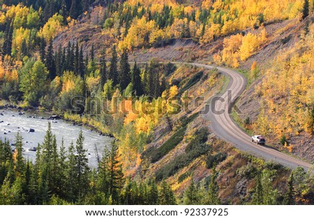 Autumn colored trees along mountain road in British Columbia - stock photo