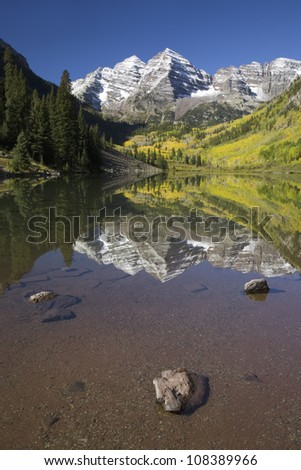 Autumn colors of Aspens reflecting in lake under Maroon Bells, Colorado - stock photo