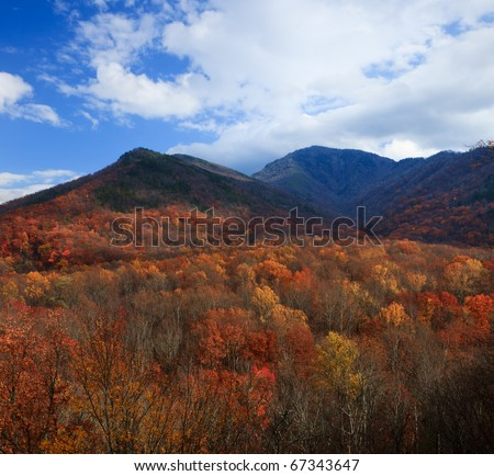 Autumn colors over the mountains with blue sky - stock photo