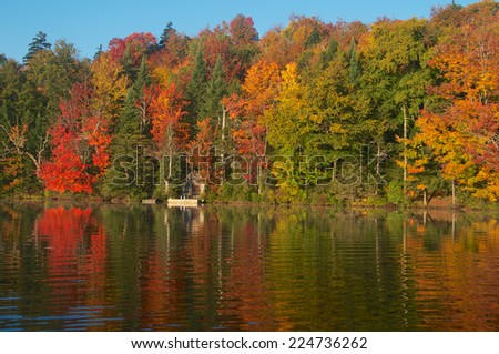 Autumn colors surround the dock stretched peacefully out into the lake - stock photo