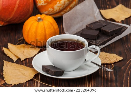 Autumn Concept. Cup Of Tea Or Coffee. Dried Fruits. Pumpkins. Dark Chocolate. Wooden Background. - stock photo