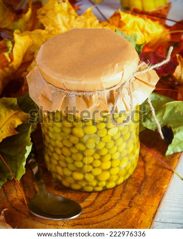 Autumn concept. Preserved food in glass jar on a wooden board. Marinated peas - stock photo