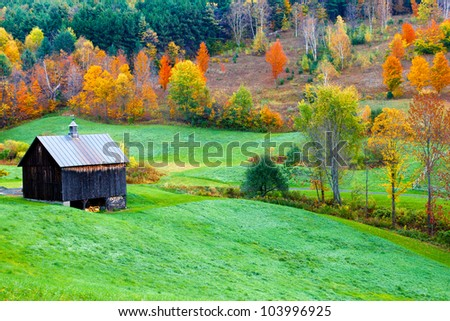 Autumn country scene with a vintage barn and colorful trees