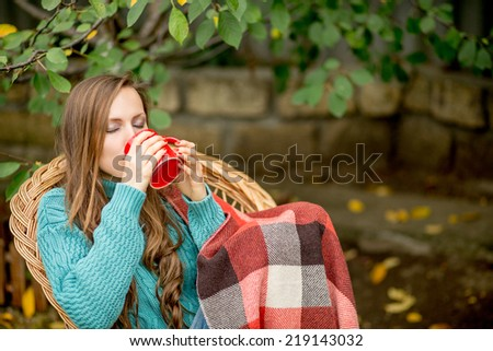 Autumn drinking hot tea woman in autumn garden sitting in wicker armchair wrapped in plaid woolen blanket - stock photo