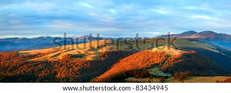 Autumn evening plateau landscape with lust golden sunlight on mountains and pink evening glow in sky. Two shots stitch image. - stock photo