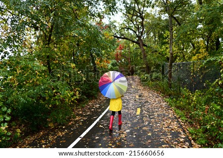 Autumn / fall concept - woman walking in forest with umbrella in rain. Girl enjoying rainy fall day. - stock photo