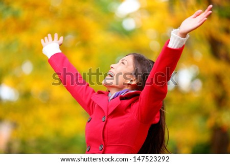Autumn / fall woman happy in free freedom pose with arms raised up towards the sky with smiling cheerful, elated expression of happiness. Beautiful girl in colorful forest foliage outdoor. - stock photo