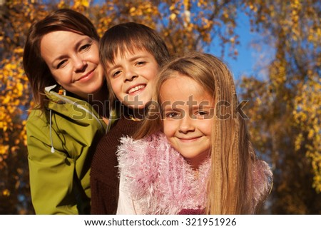 Autumn family portrait in the sunny forest - focus on little girl - stock photo