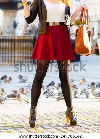 Autumn fashion. Fashionable woman in stylish shoes boots with handbag bag outdoor city street with pigeons - stock photo