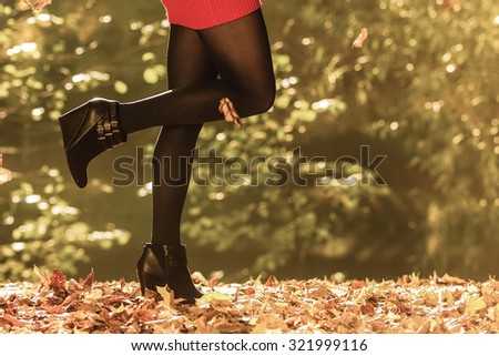 Autumn fashion. Female legs in black pantyhose and stylish fashionable shoes boots, outdoor golden leaves - stock photo