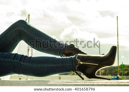Autumn fashion outfit. Fashionable woman long legs in denim pants black stylish high heels shoes outdoor on city street - stock photo