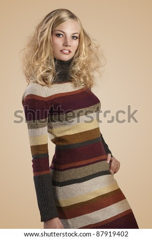autumn fashion shot of a natural blonde beauty wearing a striped wool dress - stock photo