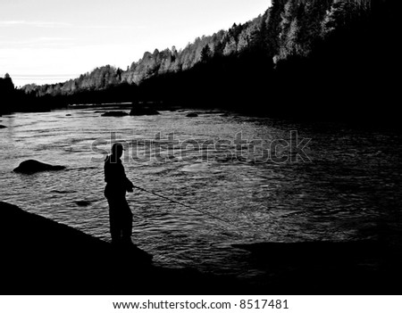 autumn fishing in a river just before sunset - stock photo