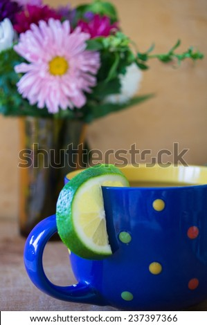 autumn flowers in vase and tea with lime - stock photo