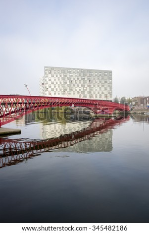 Autumn foggy day, Amsterdam canal in the mist with a red metal bridge, The Netherlands
