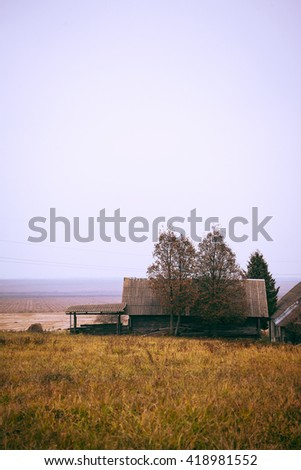 autumn foggy village landscape with trees and old wooden house