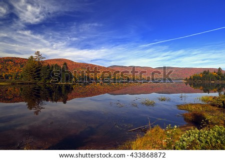 Autumn forest reflected in water. Colorful autumn morning in the mountains. Colourful autumn morning in mountain lake. Colorful autumn landscape. Parc national Mont Tremblant. Quebec. Autumn in Canada