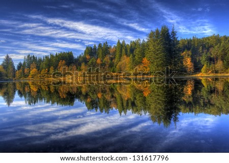 Autumn Forest Reflection in a lake on mount Floyen in Bergen (Norway) - stock photo