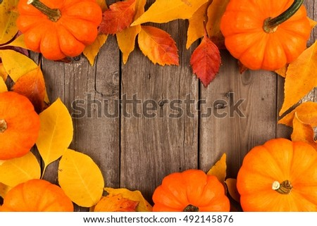 Autumn frame of pumpkins and leaves against a rustic old wood background