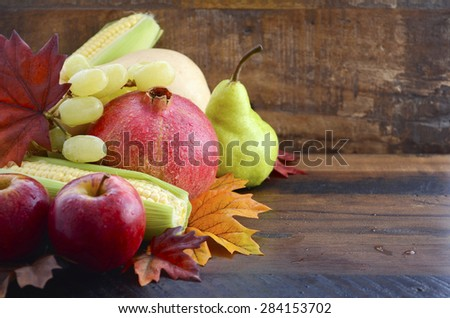 Autumn Fruit and Vegetable Background with fresh butternut pumpkin, grapes, leaves, apples, pear, pomegranate, and corn, with copy space for your text here..  - stock photo