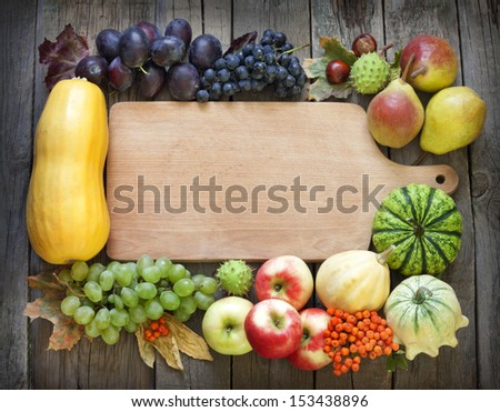 Autumn fruits and vegetables and empty cutting board - stock photo