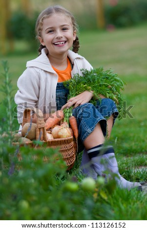 Autumn gardening - lovely girl with picked vegetables in basket - stock photo