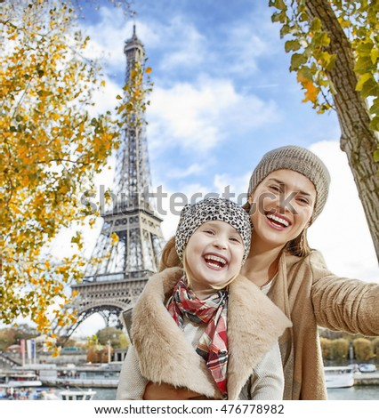 Autumn getaways in Paris with family. happy mother and child travellers on embankment near Eiffel tower in Paris, France taking selfie while sitting on the parapet