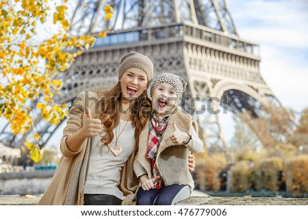 Autumn getaways in Paris with family. Portrait of happy mother and child travellers on embankment near Eiffel tower in Paris, France showing thumbs up