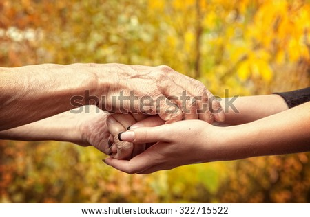 Autumn. Hands of an elderly senior holding the hand of a younger woman - stock photo