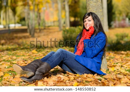 Autumn happy fashion woman sitting in park. Beautiful caucasian brunette enjoying leisure on fall season. - stock photo