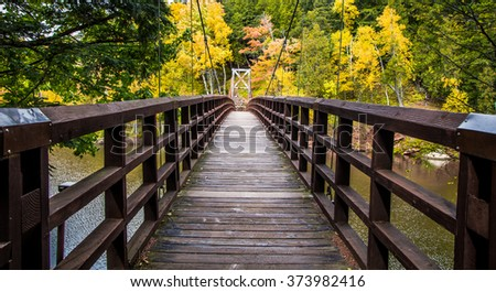 Autumn Hike In Michigan On The North Country Trail. Bridge over the Black River in the Ottawa National Forest on the North Country Trail in Michigan. - stock photo