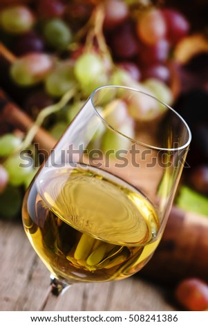 Autumn ice wine, ripe grapes and dried leaves, vintage wooden background, selective focus