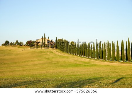 Autumn in Italian Toscana with colorful trees and farm house in the background