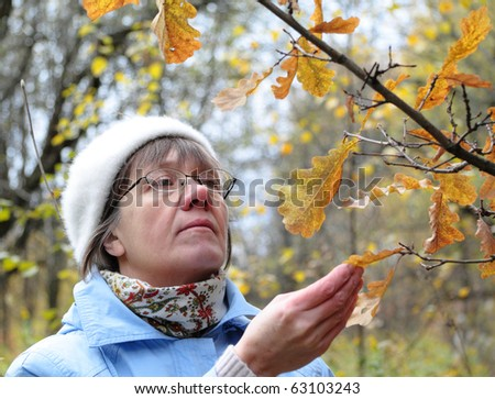 autumn in nature, contemplate middle-aged woman - stock photo
